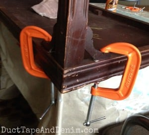 My hubby glued the decorative pieces back on my coffee table with gorilla glue and C-clamps | DuctTapeAndDenim.com
