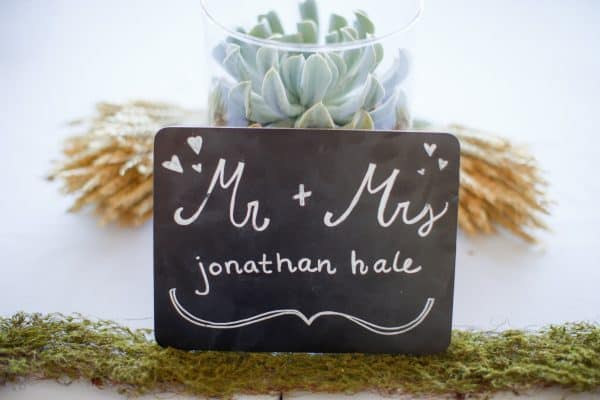 Mr and Mrs chalkboard sign, centerpiece on head table at wedding | DuctTapeAndDenim.com