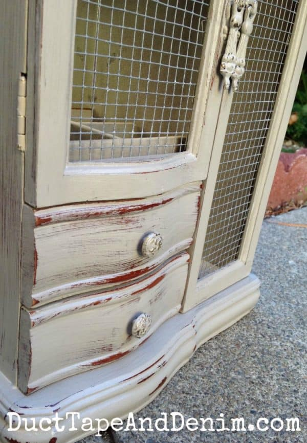 Close up of the distressing on painted jewelry cabinet with hardware cloth