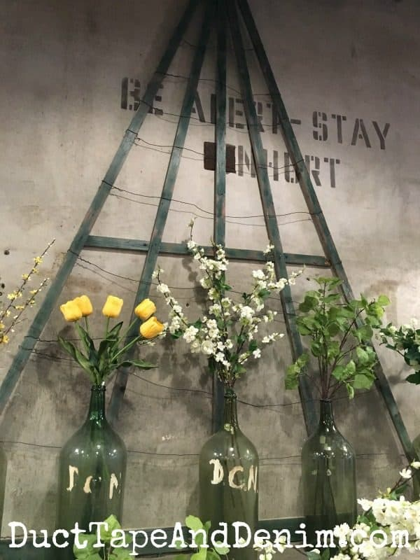 Trellis, silk flowers, vintage bottles display in Magnolia Market | DuctTapeAndDenim.com
