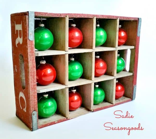 Shiny Brite ornaments displayed in vintage soda crate.