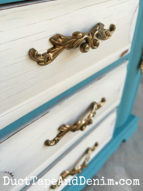 Close up, finished handles on thrift store jewelry cabinet