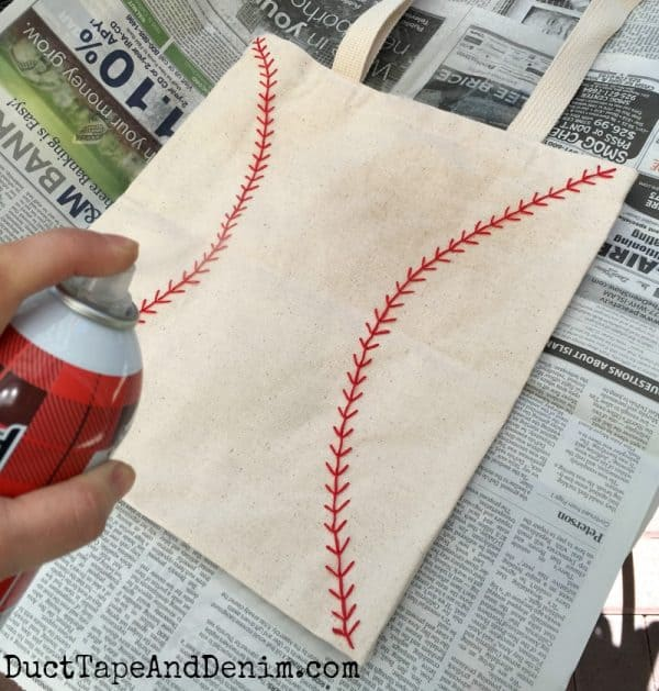 Spraying baseball tote bag with Scotchgard Fabric Protector | DuctTapeAndDenim.com
