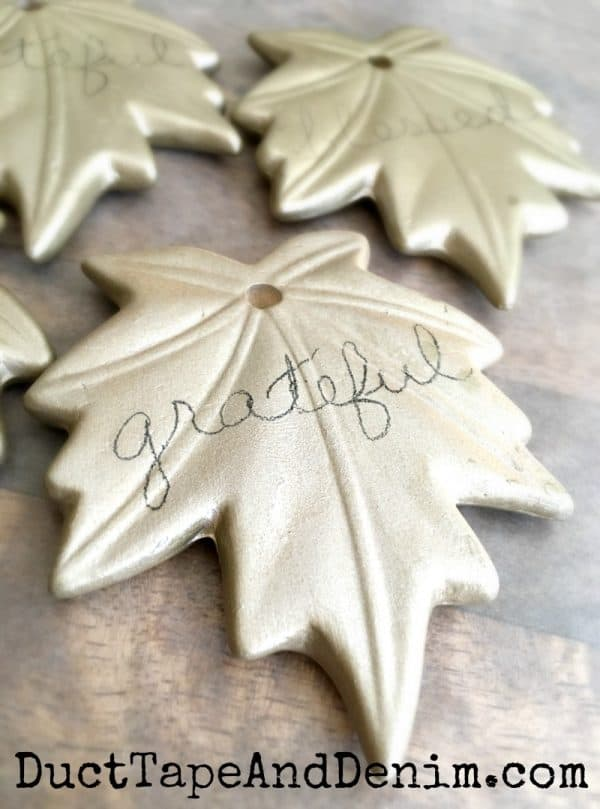 Wrote words in pencil on leaf ornaments to trace with paint
