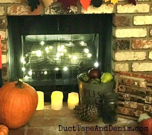 Pine cone mason jar in fall fireplace vignette | DuctTapeAndDenim.com