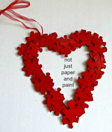 Red puzzle piece heart wreath. More DIY Valentine's Day wreath ideas on DuctTapeAndDenim.com