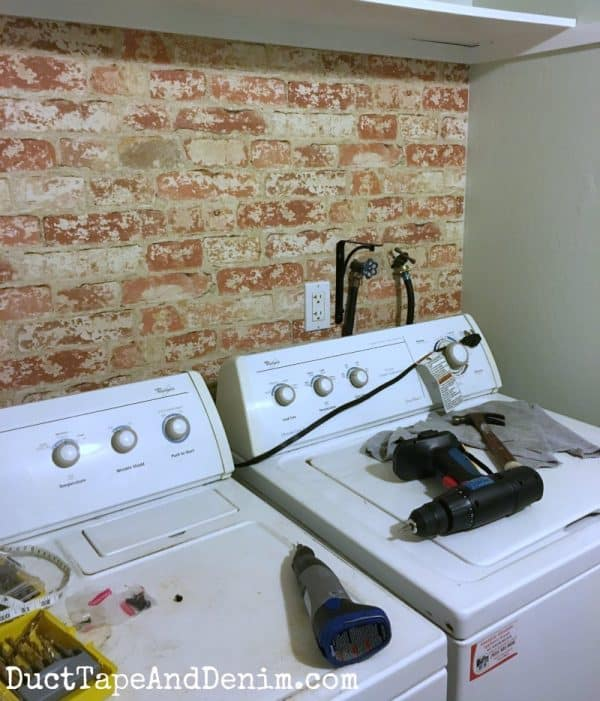 Brick wallpaper up in my laundry room | DuctTapeAndDenim.com