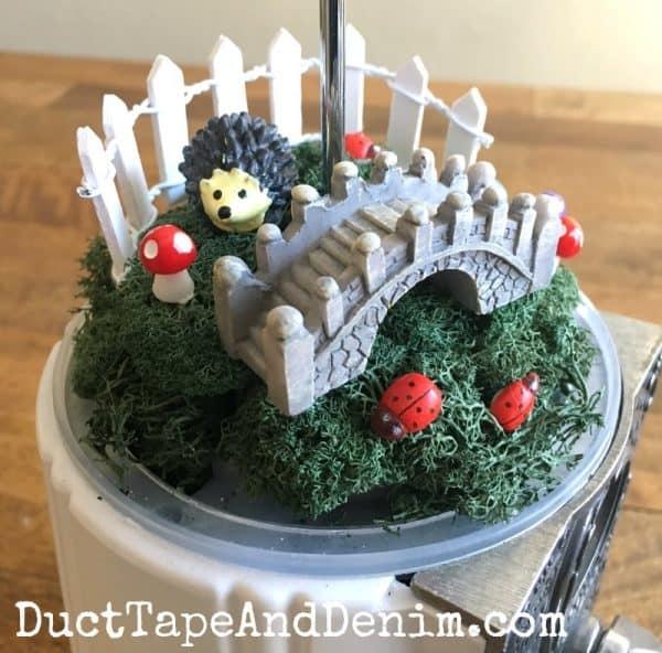 Fairy garden bridge gate hedgehog in thrifted gumball machine | DuctTapeAndDenim.com