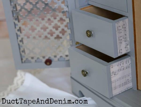 Music scrapbook paper on upcycled jewelry cabinet drawers | DuctTapeAndDenim.com