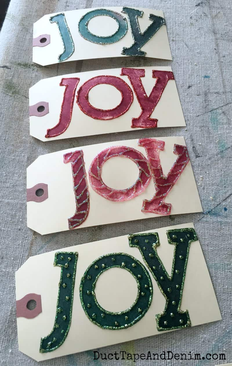 JOY Christmas gift tags drying. See how to make more holiday gift tags on DuctTapeAndDenim.com