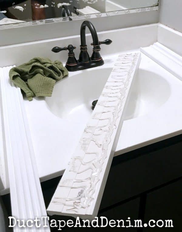 Gluing frame to bathroom mirror   DuctTapeAndDenim.com