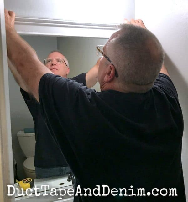 Putting up bathroom mirror frame | DuctTapeAndDenim.com