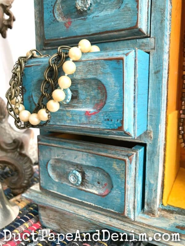 Close up of drawers on boho blue jewelry cabinet | DuctTapeAndDenim.com