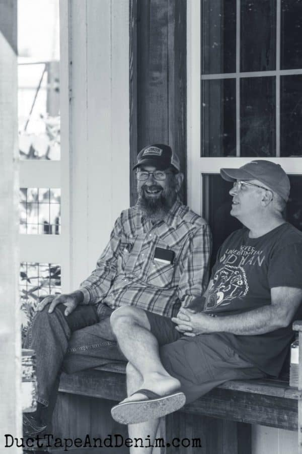 Men sitting on the porch at Magnolia Seed and Supply | DuctTapeAndDenim.com