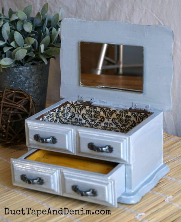 gray jewelry box opened showing decoupage inside