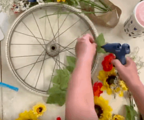 gluing flowers on wheel wreath